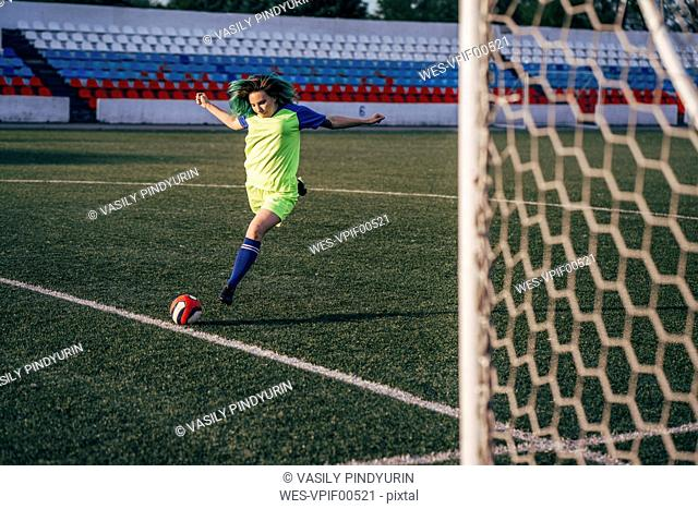 Young woman playing football on football ground shooting the ball