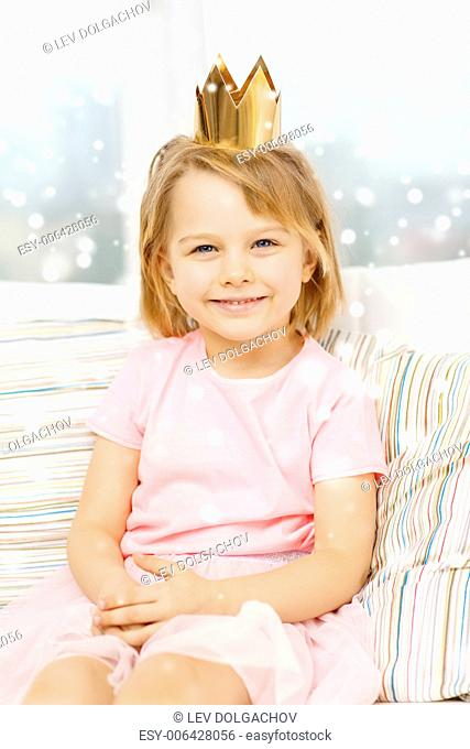childhood, people, holidays and happiness concept - smiling little girl in crown sitting on sofa at home