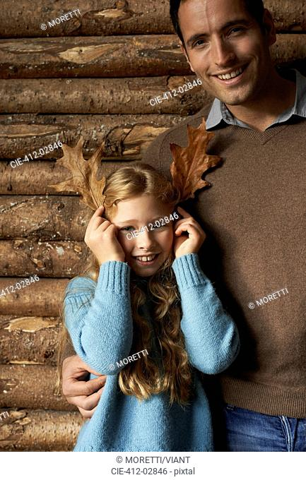 Girl using leaves as antlers with smiling father