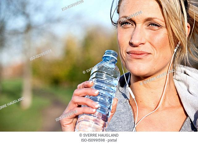 Mid adult woman drinking from water bottle outdoors
