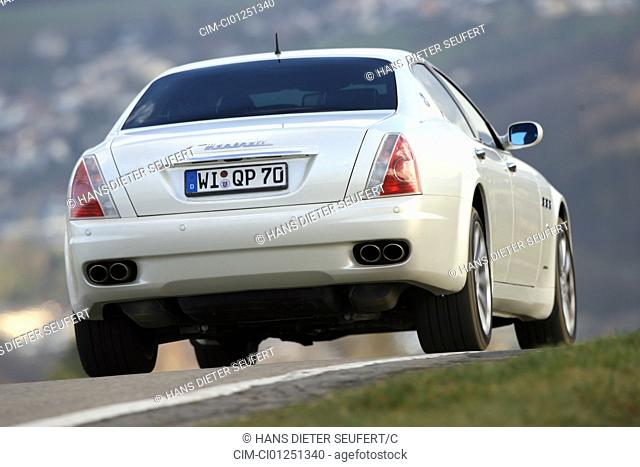 Maserati Quattroporte automatic, model year 2007-, white, driving, diagonal from the back, rear view, country road