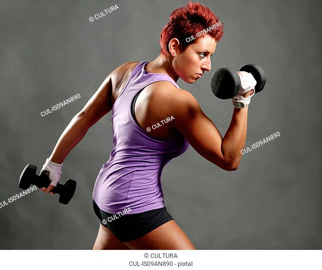 Side view studio portrait of young woman poised with dumbbells
