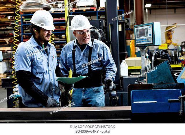 Workers talking in metal plant