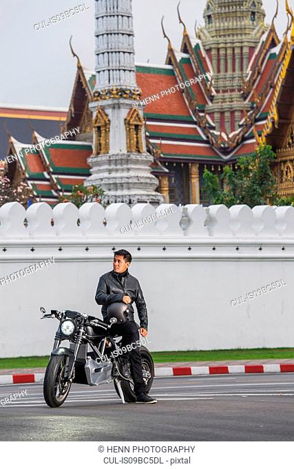 Man with electric motorbike by royal palace, Bangkok, Thailand