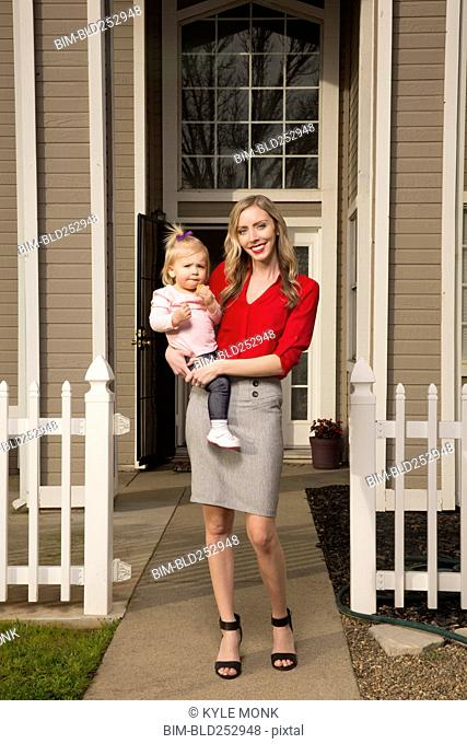 Caucasian mother posing near house with baby daughter