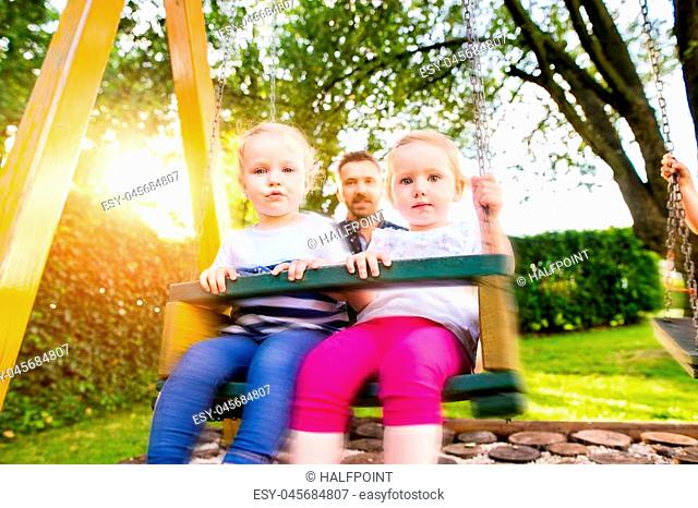 Young hipster father pushing his daughters on swing in a park. Happy girls outdoors in the summer