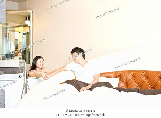 Young woman looking at asleep man in the bedroom at home