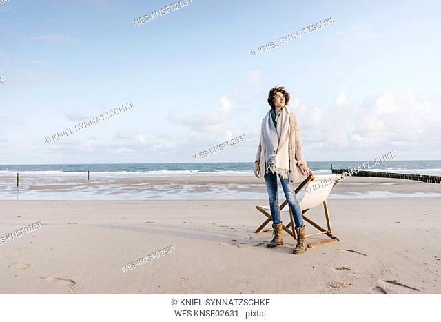 Woman standing next to deckchair on the beach