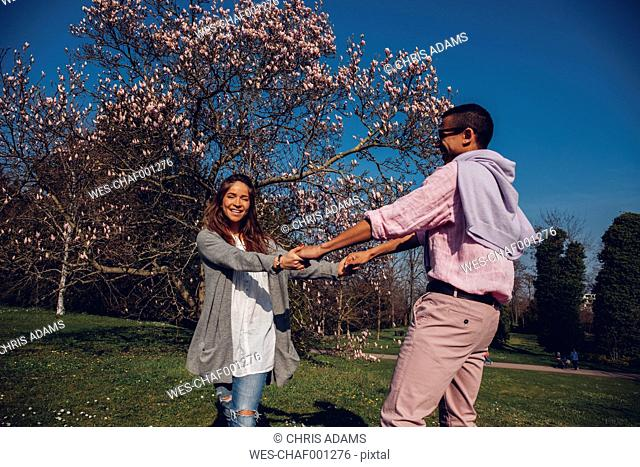 Happy young couple holding hands in park