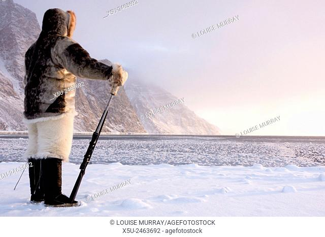 One of the last remaining Inughiut subsistence hunters Naimanngitsoq Kristiansen stands on watch with his rifle for marine mammals at the ice edge
