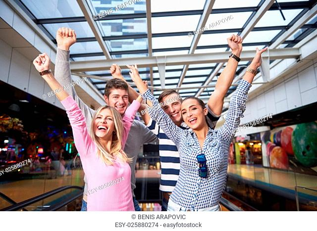 group of happy friends in shopping mall have fun