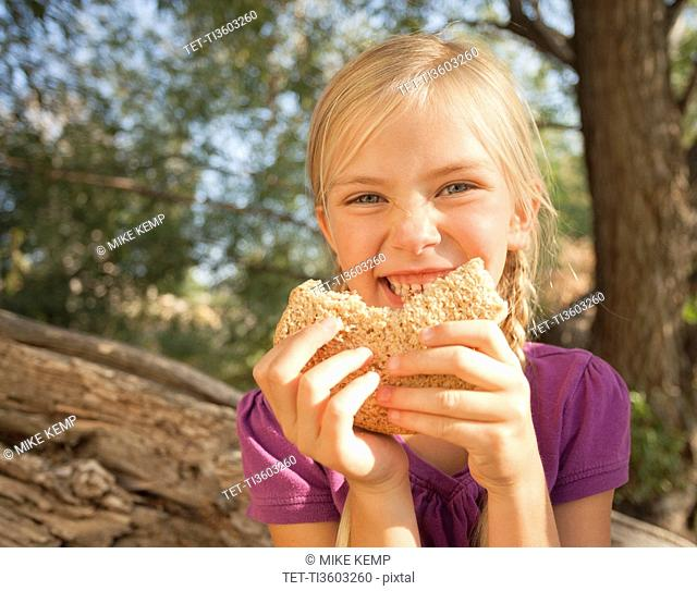 Little girl 4-5 eating peanut butter and jelly sandwich