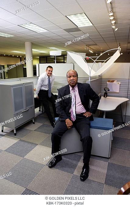 Portrait of businessmen at office cubicles