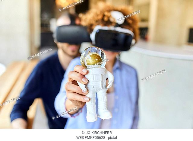 Man and woman wearing VR glasses holding astronaut figurine