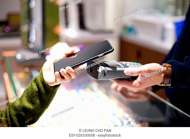 Woman paying with NFC technology on smart phone at shop