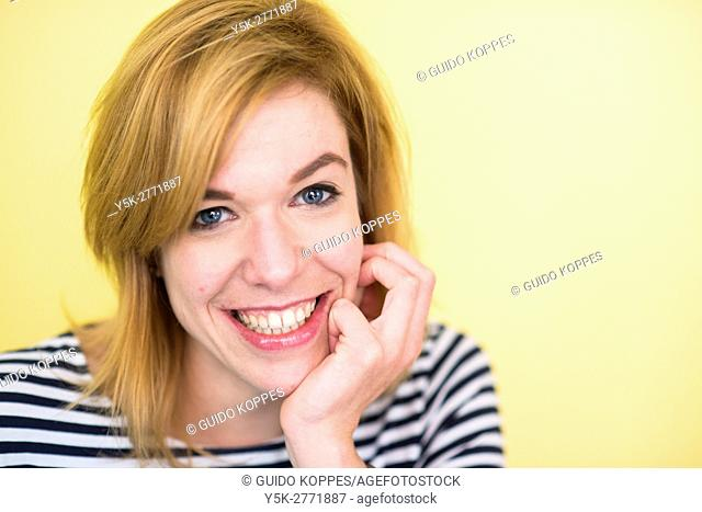 Tilburg, Netherlands. Portrait of a happy, mid adult caucasian woman smiling, in front of a yellow background
