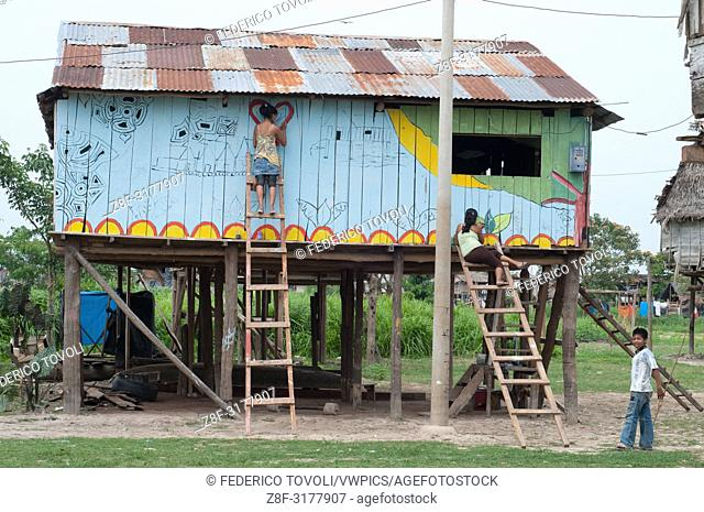 Painting the houses in Belen during the festival. Peru