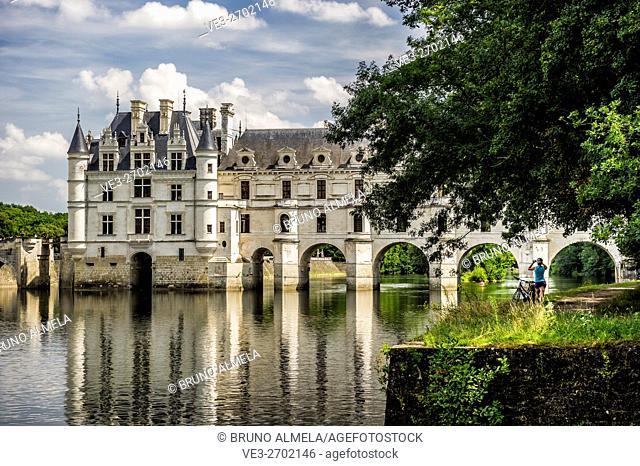 Tourist photographing the Chenonceau castle from Le Cher River (department of Indre-et-Loire, region of Centre-Val de Loire, France)