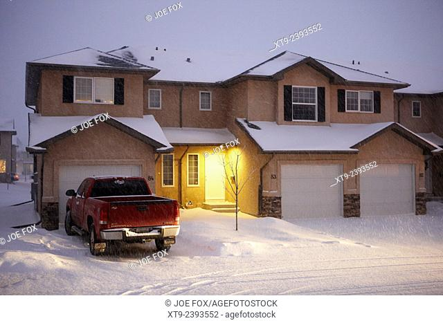 truck parked outside house with snow falling in residential neighborhood in Saskatoon Saskatchewan Canada