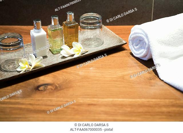 Perfume bottles and frangipani flowers on tray