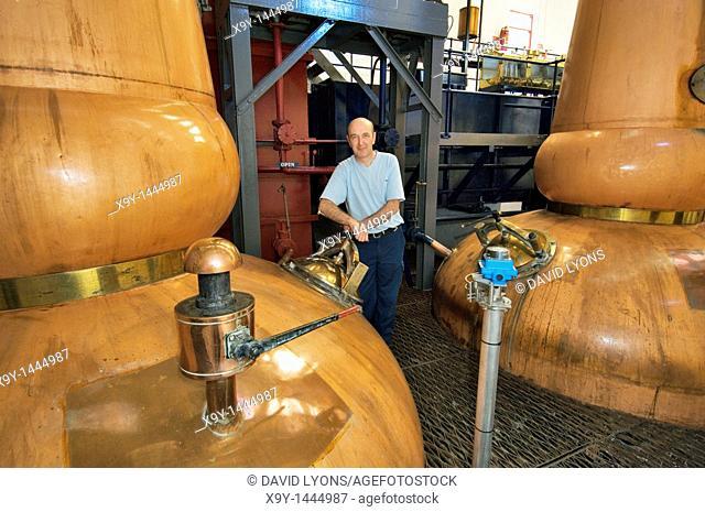 Tobermory Whisky Distillery, Isle of Mull  Scotland  Still man Ruairaidh Currie  Traditional copper pot stills in the Still Room