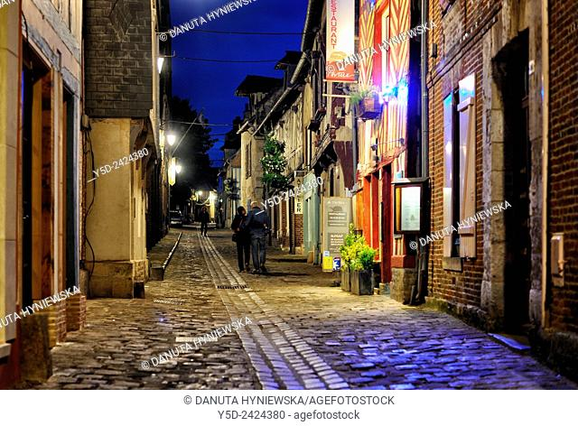 mature couple walking in the old town of Honfleur at night, Normandy, France