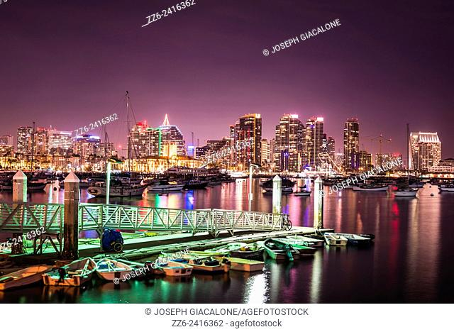 Night scene of lights at a boat dock and the San Diego Downtown Skyline. San Diego, California, United States