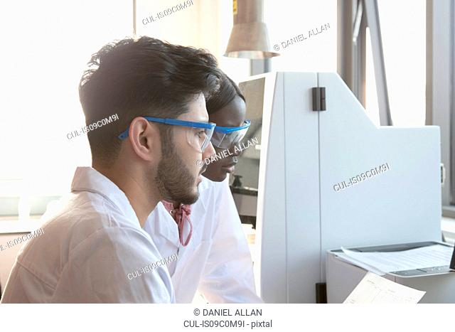 Young female and male scientists looking at results in laboratory