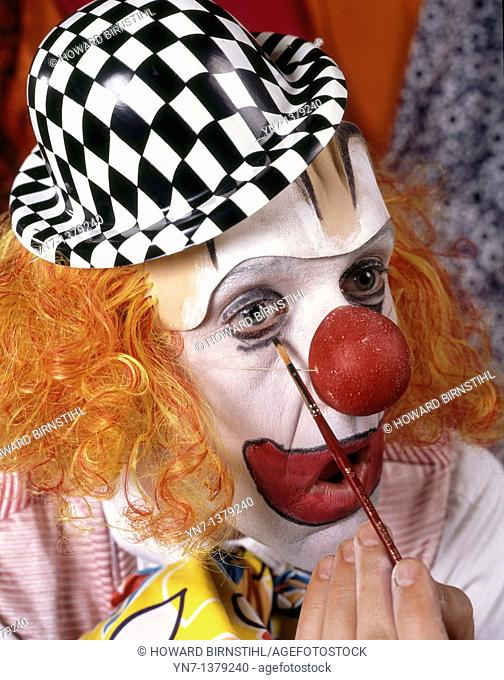 close up of clown putting the finishing touches to his make-up