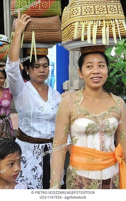 Ubud (Bali, Indonesia): women in traditional dress, carrying a basket with offerings on their heads, going to a ceremony in a Hindu temple