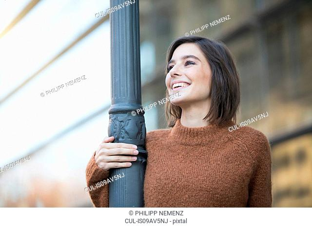 Mid adult woman holding city lamppost