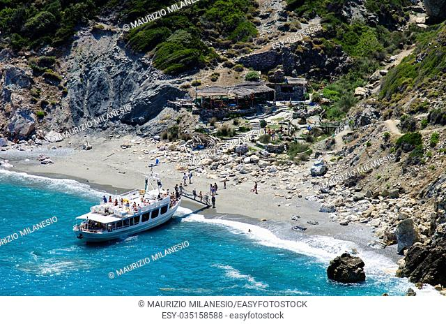 Tourist boat landing on the beach of Kastro at Skiathos on the bottom a restaurant bar and the typical island's vegetation on the cliff