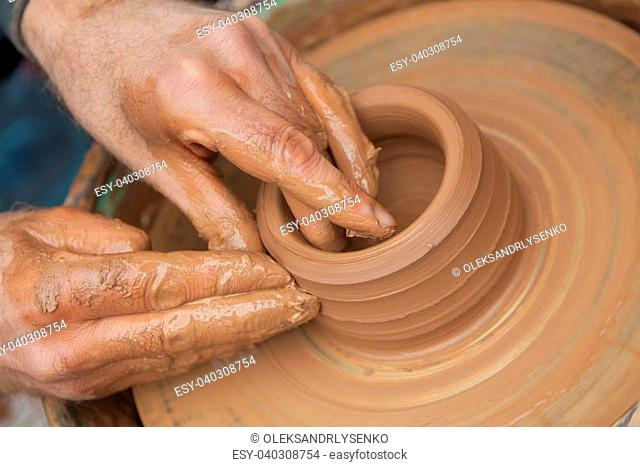craftsman works in clay pot outside