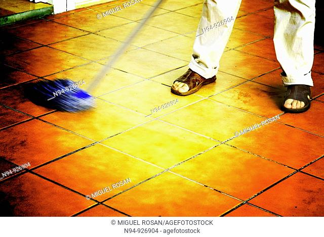 Man mopping the floor of the terrace