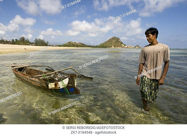 A fisherman next to his boat on the shore of Kuta beach, a fishing village south of Lombok Indonesia