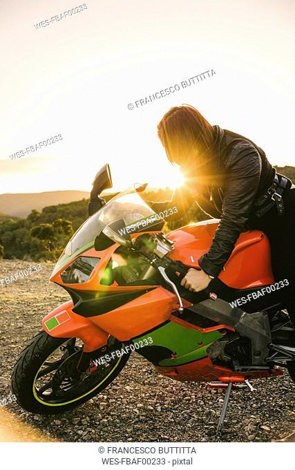 Italy, Elba Island, female motorcyclist against the sun