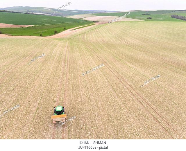 Aerial View Of Loading Fertilizer Into Spreader On Tractor