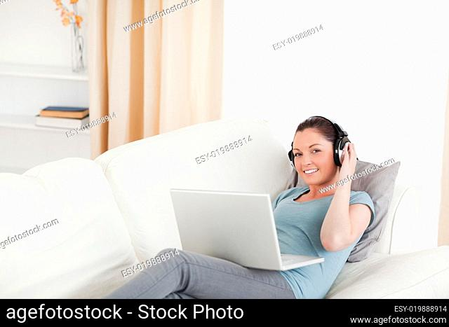 Gorgeous female with headphones relaxing on her laptop while lyi
