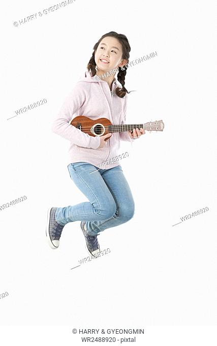 Smiling school girl in casual clothes jumping playing an ukulele
