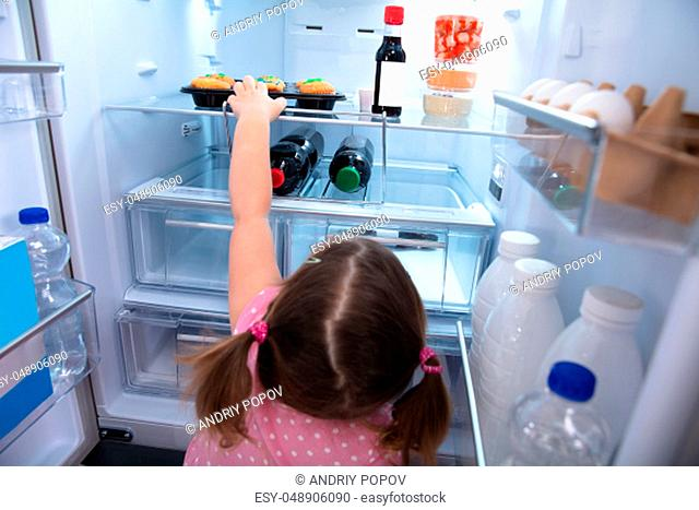 Cute Little Girl Trying To Reach Out And Pick Cupcakes From Fridge At Home