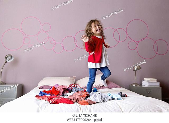 Little girl dancing on a pile of laundry on her parents' bed