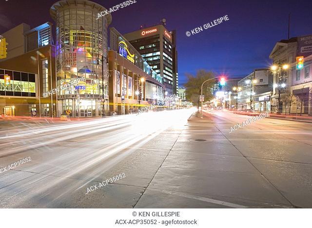 Traffic light trails and MTS Centre Arena at night. Portage Avenue, Winnipeg, Manitoba, Canada