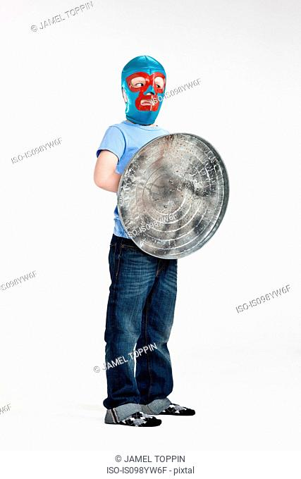 Boy wearing mask holding dustbin lid