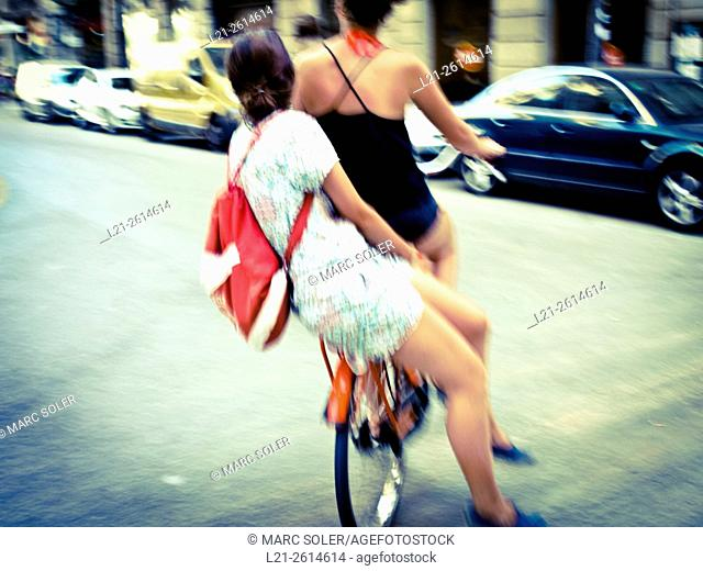 Women riding bicycle together on a city street. Barcelona, Catalonia, Spain
