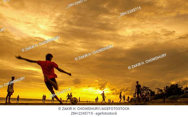 Children are palying football during sunset in kuakata sea beach in Bangladesh