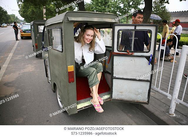Tourist riding in cycle rickshaw, Hutong District, Beijing, China, Asia