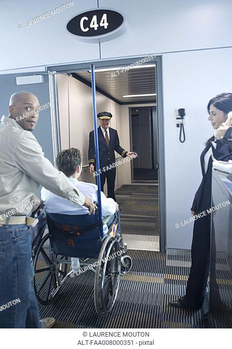 Man with traveler in wheelchair at boarding gate