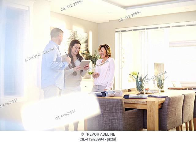 Interior designer using digital tablet in consultation with couple in dining room