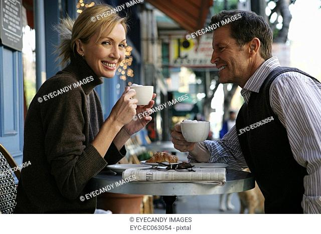 Mature couple at an outdoor cafe looking at camera