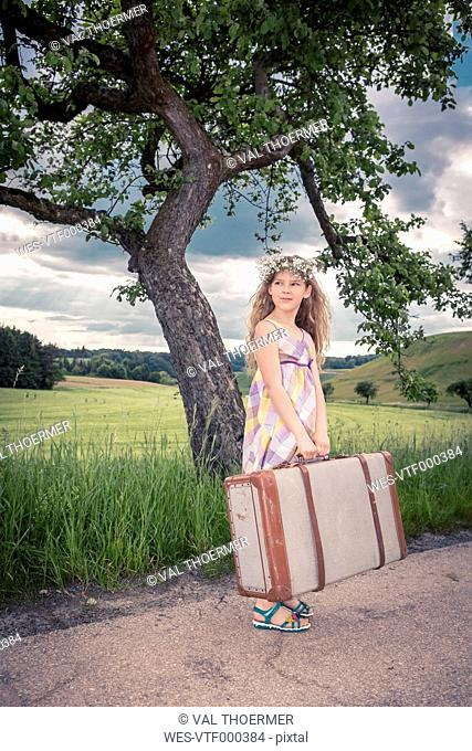 Germany, Bavaria, Girl with old suitcase waiting at roadside